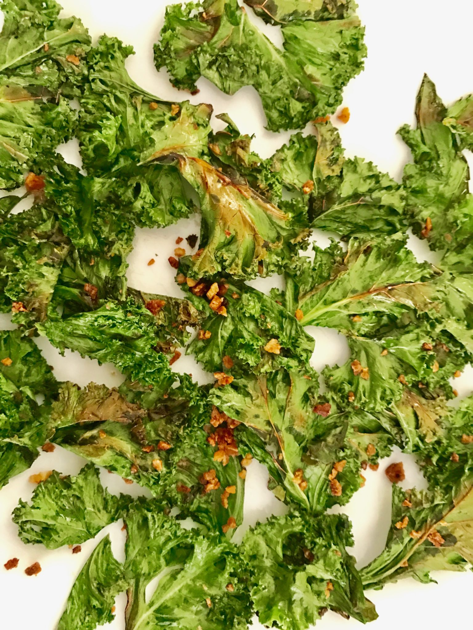 kale chips are being cooled on a plate