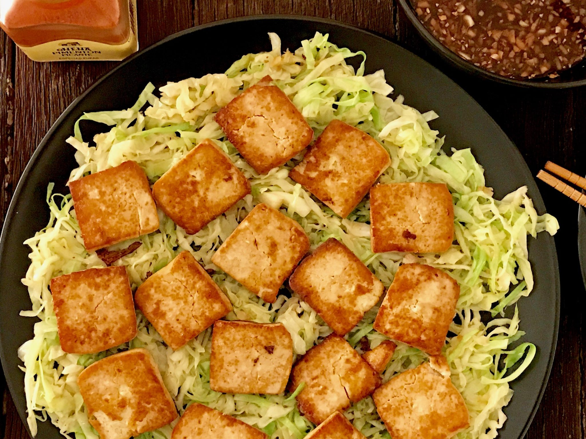 arranging the fried tofu on the sauteed cabbage